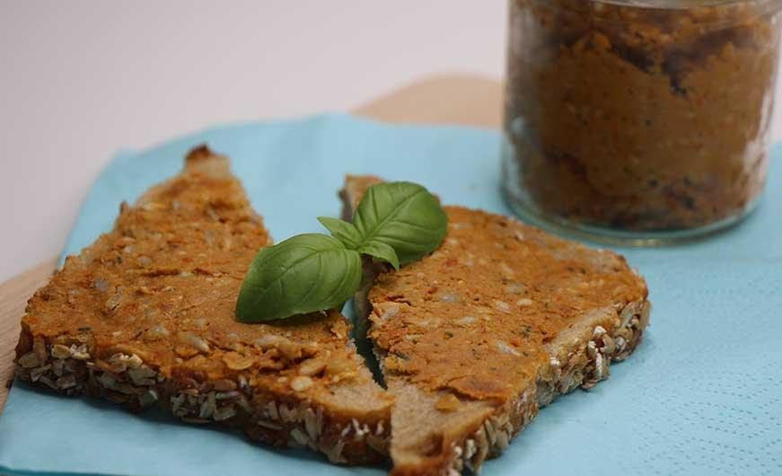 Veganer Brotaufstrich auf Kartoffelbrot mit Basilikum garniert