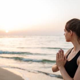 Frau in Yogapositon- Handflaechen aneinander blickt aufs Meer und den Sonnenuntergang am Horizont