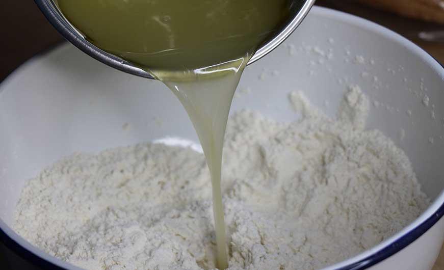 WWasser, Oel, Hefemischung wird in die Süssel zu Mehl geschuettet
