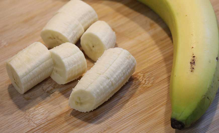 Banane ganz und geschaelt und in Stuecke geschnitten