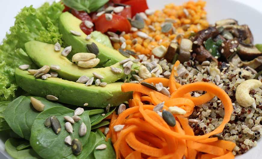 Bowl vegan Nahaufnahme mit Avocado Karotten Babyspinat und mehr