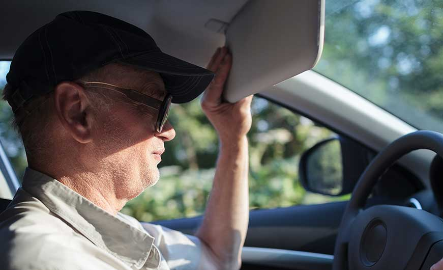 Mann mit kopfbedeckung schützt sich im auto vor der sonne mit der sonnenblende