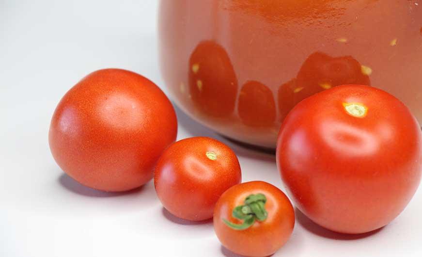 tomaten rot vor glas mit passierte tomaten