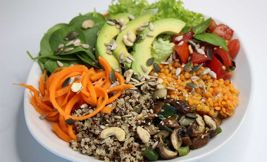 vegane bowl mit Quinoa, Pilzen, Linsen, Tomate, Avocado, Salat, Spinat, Nuesse