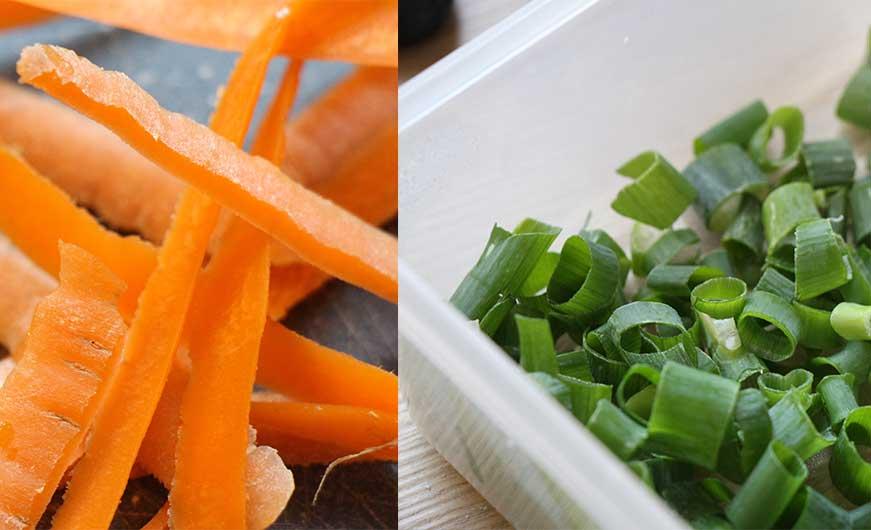 Karotten Schalen und box mit geschnittenen Fruehlingszwiebeln