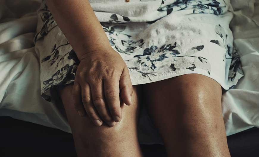 ältere Frau hält ihr Knie