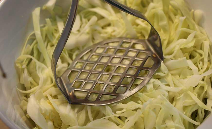 Kohlstreifen mit Kartoffelstampfer stampfen
